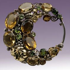 Dorrie Nossiter. Arts and Crafts circular crescent brooch. Silver, gold, citrine, peridot and tourmaline. Diameter: 5.50 cm (2.17 in). Fitted case. Sold by Tadema Gallery.
