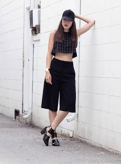 17 Ways to Wear Longer Shorts This Summer: This combination of high-waisted shorts, a crop top, and baseball cap is sporty and chic.