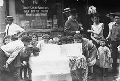 Children gathered around and licking blocks of ice on hot day between 1910 and 1915.