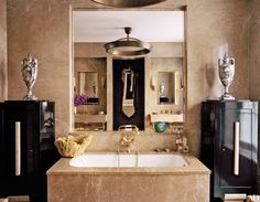 Marc Jacobs' bathroom featuring a marble-clad tub flanked by 19th-century urns on lacquer cabinets | archdigest.com