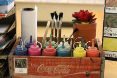 Coca Cola box for paint storage? 🎨 From ketchup bottles for tempera paint, to a roll of paper ready to go, this is a great idea to keep on a shelf or even a great moveable storage idea! 💡 What paint storage ideas do you use? Preschool Classroom Setup, Reggio Classroom, Preschool Centers, Classroom Environment, Classroom Organization, Classroom Ideas, Future Classroom, Preschool Ideas, Classroom Management