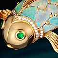 An opal, emerald and diamond brooch, Oscar Heyman & Brothers.  Photo Bonhams in the form of a fish, with scales of opals,...