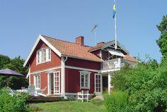 Skärgårdsromantik bland grönskande ängar och skog med historia från 1850-talet rött hus vita knutar