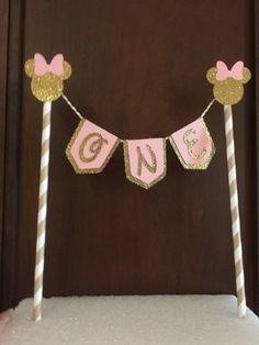 Minnie Mouse banner cake topper. Perfect for your little ones first birthday. Can also change the numbers for a different age. Numbers on banners can be replaced with names upon request. Anything over 5 letter will have an additional charge Flags measure 1.5X 1.75.  Pink ribbon can be used instead of white and gold twine.