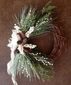 This 18 inch grapevine wreath base is adorned with faux evergreen, faux iced pine needles, frosted pinecones, and ivory pearl-like berries. It is