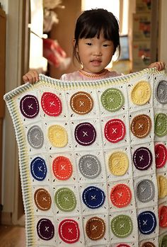 """""""Button, button, who's got the button"""" blanket? With a love of buttons and bright colors, I designed this blanket pattern to be easily created in your own color scheme and size. Make more squares and make an afghan or bedcover. Bust your stash and use your own colors to match any nursery or home decor."""