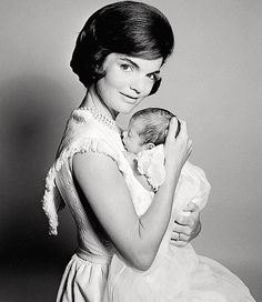 "Jackie Kennedy holds son John F. Kennedy, Jr., born November 25, 1960, 16 days after his father, John F. Kennedy won the presidential election. He was nicknamed ""John-John."" Three years later on his birthday, John F. Kennedy, Jr. would salute his father's casket at his funeral."