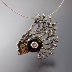 Autumnus Tvář podzimního lesa... Autorský šperk vyrobený technikou letování, s vloženým chalcedonem (oko) a skleněným kabošonem. Patinován a leštěn. Velikost šperku je cca 7 x 7,5 cm. Ač je šperk větší není nikterak těžký. Zavěšen na nerezové obruči cca 45 cm - lze upravit či vyměnit za jiný typ závěsu (kůže, řetízek). Dárkově baleno (obruč zabalena ...