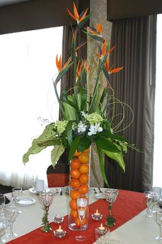 Tropical Birds of Paradise highlight this spectacular centerpiece on a glass riser filled with navel oranges. Notice the elegant table bling around the base of the riser!
