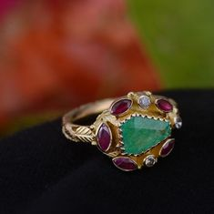 This gorgeous one of a kind ring has been handmade in our workshops. It has a central emerald, which is surrounded by rubies and diamonds. The rings is made in 18ct gold and has hand engraved botanical motifs on it.  Ring size - UK size M/ USA size 6 1/4  Ring dimensions - 14mm x 16mm  Alternative Wedding Jewellery, Alternative Engagement Rings, Emerald Diamond, Hand Engraving, Gemstone Jewelry, Jewels, Gemstones, Silver, Gold