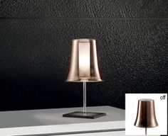 CLOCHE TABLE -  This simple and charming table lamp is part of the Cloche collection. Composed of clear glass with a shiny copper or chrome coating and inner frosted glass cylinder . The clear glass combined with either of the exterior finishes creates a two- tone effect noticeable when the light is turned on. The stem is secured to a square rust or anthracite painted base. On/off switch on cord</p>