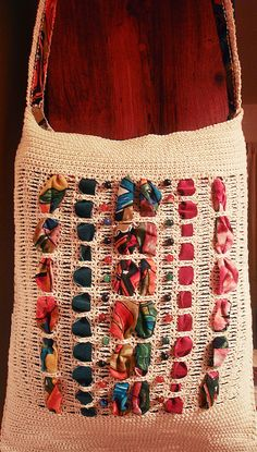 String tote, single crochet borders and strap with skip 3, chain 3 panels to accommodate interlacing fabric strips. (I used a recycled print skirt and suede strips). Bead accents from thrifted necklace. Lined in skirt fabric. Original design, very easy.