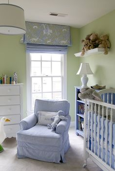Adorable blue & green nursery design with green walls paint color, white crib, blue bookshelf, blue glider, drum pendant with blue ribbon trim, blue & green roman shade and white chest.