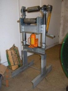 Sheet Metal Roller - Homemade sheet metal roller powered by a bottle jack and utilizing pipe sections as rollers.