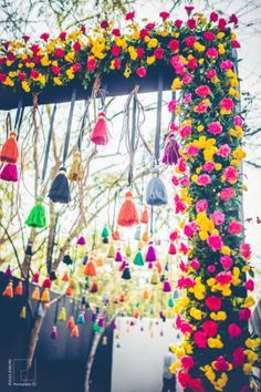 Indian Wedding Decor - Uneesh & Aashna wedding story | WedMeGood | Colorful Floral Decor with Hanging Pom-Poms #wedmegood #indianbride #indianweddingdecor #decor #pom-poms #floral #hangingdecor #colorful #quirkydecor