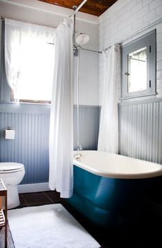 I love the blue tub and the wainscotting coupled with the subway tile.