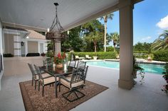 Large patio space encompasses roofed dining space with glass topped table and chairs over patterned rug, plus pool area beyond large columns.