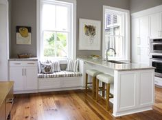 Grey walls, Kitchen Bench, and White Cabinets with warm wood floors. Good blend of warm and cool tones
