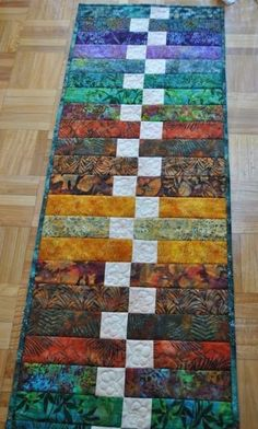 """This table runner pattern called """"Zippy Strippy"""" was featured in the McCalls Quilting July/August 2013 issue. Table Runner And Placemats, Table Runner Pattern, Quilted Table Runners, Batik Quilts, Jellyroll Quilts, Scrappy Quilts, Quilted Table Toppers, Strip Quilts, Sewing Table"""