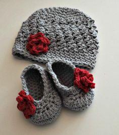 graue Babymütze und Babyschuhe mit roter Blume