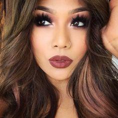 Dramatic black eyelashes and dark mauve lipstick