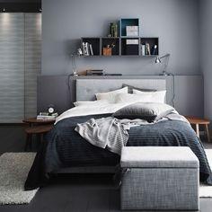 Harmaa makuuhuone, jossa ÅRVIKSAND-jenkkisänky, TUSENSKÖNA-päiväpeitto ja FJÄRA-säilytyslaatikko.