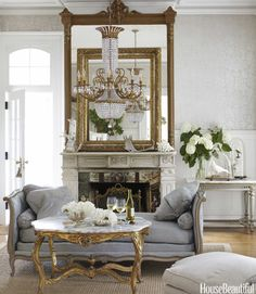 """The parlor's daybed, gilt tables, overmantel, and chandelier are all French. Brahler found just enough vintage wallpaper in France to top wainscots painted Sherwin-Williams Cloud White. The mantel shelf holds one of the designer's hallmark """"extreme juxtapositions"""": a massive empty picture frame, propped against the mirror, alongside antlers her children collected on hikes. Glass domes shelter antique taxidermy.   - HouseBeautiful.com"""