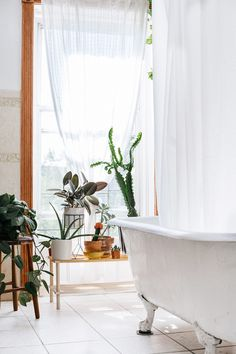 Bright Swedish-inspired bathroom with a freestanding tub, a hanging curtain, and indoor plants