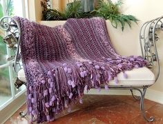 "One I just finished. I JUST LOVE making these chunky, cozy and very simple afghans. I used Homespun Barouque for the main color, a combo of 1 strand each of short eyelash and a furry yarn for the fuzzy stripes and a few rows of Mauve Metallic Scarf yarn for the contrasting stripes. I added a Funky 11"" fringe made up of about 8 different yarns (130 total fringe sets). Finished size-50"" X 94"" with fringe. Using up a lot of my leftover yarns!"