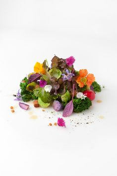 Daniel Zeal's petit lettuce salad with edible flowers, micro greens, baby vegetables, house-smoked bacon, 50 year Sherry-maple vinaigrette, and brown butter toasted croutons. - Courtesy of The Chef's Garden