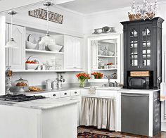 Open shelving, a skirted sink cabinet, and a shimmering chandelier provide Parisian charm in this cottage kitchen. A black hutch-style cabinet with plenty of patina gains added function with chalkboard paint./