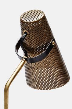 Lampe de table avec un abat-jour en laiton perforé avec une base en métal noir.