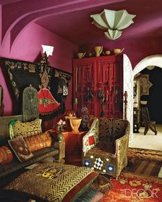 An Afghan warlord's bed serves as a sofa in the ground-floor sitting room, and the pillows are covered in Kuba cloth from Congo; a wool Berber cape hangs on the wall, and the Musharabi cabinet is custom made.
