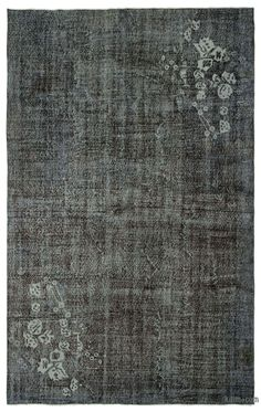 """For a contemporary look with abstract appeal, this grey over-dyed rug is skillfully crafted by the revitalization of a hand knotted vintage Turkish rug. Made from wool on cotton, this """"distressed"""" rug measures 196 cm x 313 cm. The process in creating these works of art begins by shearing to lower the pile and to help """"distress"""" them. They then undergo a series of processes to remove the color. They are now ready to be dyed in one color, a stage that can be repeated several times to reach th…"""