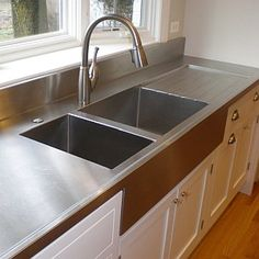 Farmhouse inspired kitchen work surface. Stainless steel counter top with integrated sink and drain board!