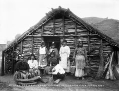 Group outside a kauta (Maori cooking house) at Parihaka Pa with buckets and kete. Most of the women wear white feathers in their hair and some hold poi. Four of the women have dark marks on their cheeks. In the foreground a woman is scraping potatoes with a shell. Photograph taken by William Andrew Collis circa 1900.