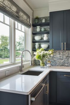 The glass mosaic backsplash in shades of swirled blues and grays by The Tile Shop is tempered by a creamy- white quartz countertop by Caesarstone. Semi-Pro kitchen faucet by American Standard.