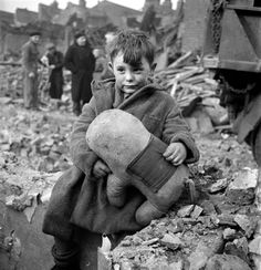 Abandoned boy holding a stuffed toy animal amid ruins following German aerial bombing of London, 1945