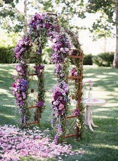 Gorgeous arch decorated in various shades of purple flowers. #afairytalewedding #weddingdecor #weddingplanning #weddingflorist