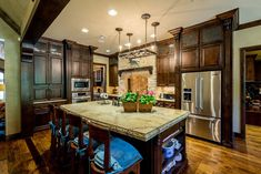 traditional-kitchen-with-hardwood-floors-dark-cabinets-light-stone-counters
