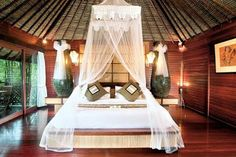 Bed room with Bali bed under native bamboo - nipa ceiling....
