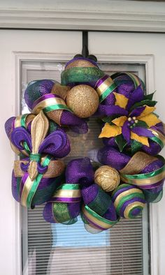 This Mardi Gras wreath is made of purple mesh deco along with gold and green mesh and Mardi Gras striped ribbon. Also on this wreath is a purple, gold and green Fleur de Lis and glittered pointsettia and ornaments. Wreath measures approximately x x Mardi Gras Wreath, Mardi Gras Decorations, Mardi Gras Party, Christmas Decorations, Christmas Trees, Holiday Wreaths, Holiday Crafts, Holiday Fun, Holiday Decor