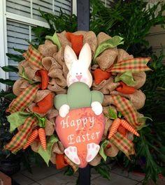 une couronne de Pâques décorée de rubans, carottes en tissu et lapin