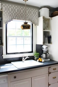The link is for a lovely DIY fabric-wrapped stencil cornice board... but I just loved how it's paired with the campaign fixtures on the cabinets!!