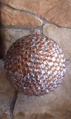 Upcycle gazing ball for the garden made with bowling ball.  This ball was a swirled gold color, 2 bags of glass gems (2 colors), 1 tube of Goop for crafts
