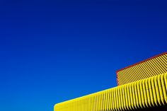 Moving away from his usual reportage style, London-based photographer Steve Bainbridge has a new ongoing series where he loves to take photographs of brightly coloured buildings against cloudless blue...