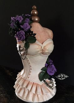 Hand made clay mannequin with slightly steam punk antique corset and floral arrangement.. This was used as a keepsake cake topper for a dress cake. By Kathy Peterson / Artisan Petal Designs.
