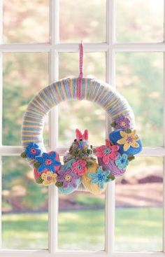Easter Bunny Wreath Crochet Pattern~Celebrate the Easter season with a colorful wreath! Crochet the flowers, leaves, bunny ears and collar to embellish the pompom bunny and easy-wrap eggs.
