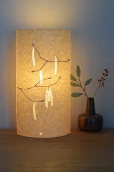 Glowing hazel catkins table lamp made from lasercut parchment by Hebden Bridge designer/maker – Hannah Nunn. We ship worldwide from our website www.hannahnunn.co.uk