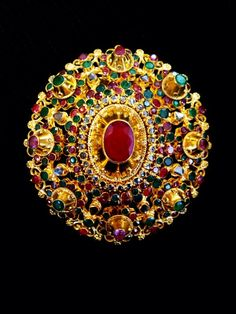 Thailand: 19th century Gold pendant of complex construction,richly ornamented with very fine rubies,emeralds and clear stones,which can also be worn as a brooch.
